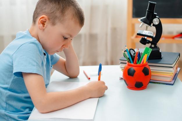 Niño de escuela sentado en el aula de casa acostado escritorio lleno de libros material de capacitación escolar