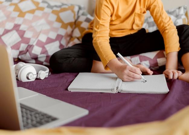 Niño de escuela sentado en la cama y escribe