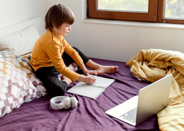 Niño de la escuela sentado en la cama escuela virtual