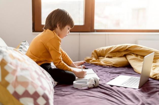 Niño de escuela sentado en la cama de lado