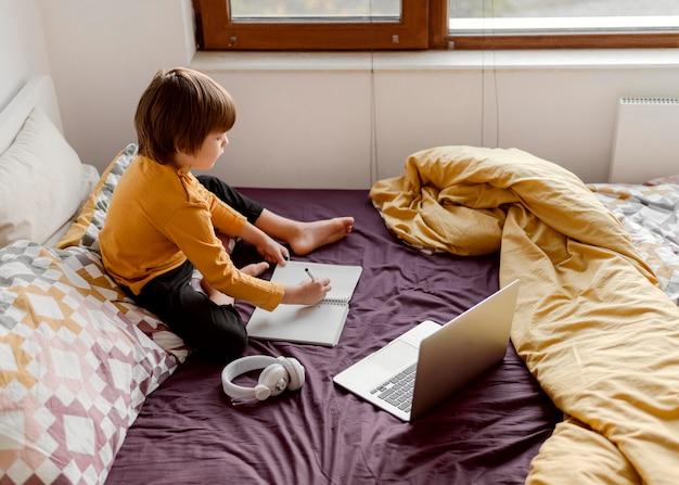 Niño de escuela sentado en la cama vista alta
