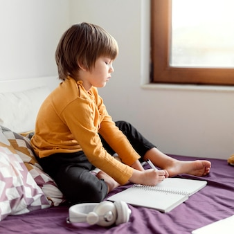 Niño de escuela sentado en la cama vista lateral