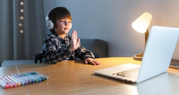 Niño de escuela tomando cursos en línea y agitando