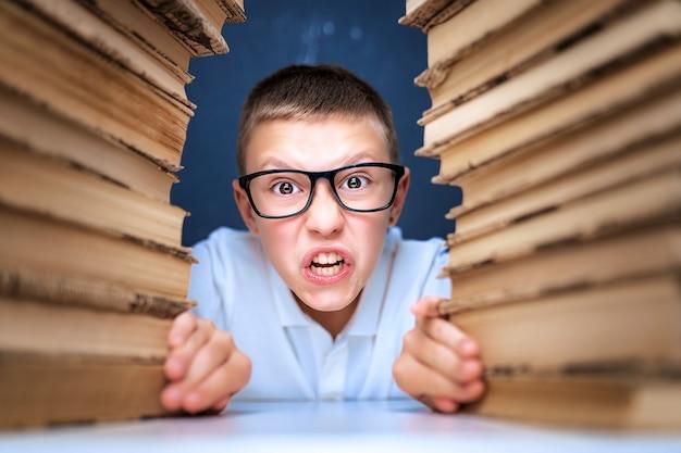 Niño de escuela en vasos sentado entre dos montones de libros