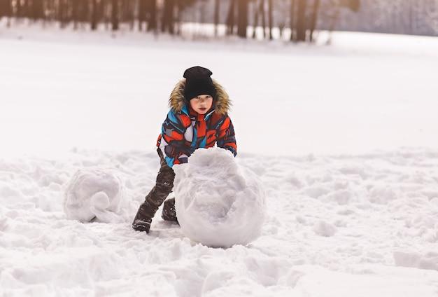 Niño esculpe una bola de nieve en invierno en el parque