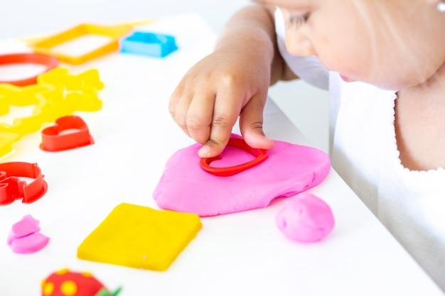 Niño esculpe de plastilina de colores sobre una mesa blanca
