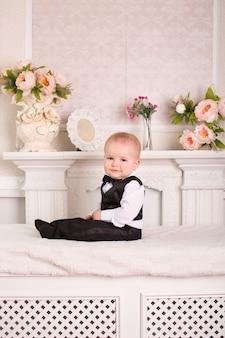 Niño en un esmoquin, sentado en la cama junto a la chimenea.