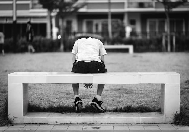 El niño estaba sentado en una triste silla cuadrada en un parque.