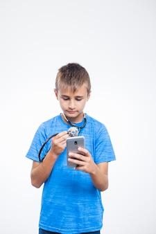 Niño con estetoscopio usando teléfono móvil
