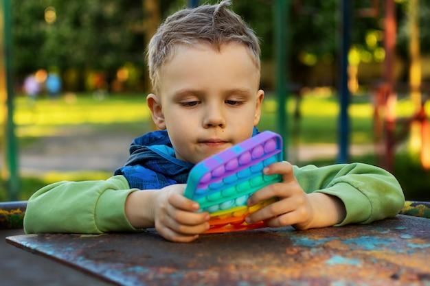 Niño con estilo sostiene en sus manos un juguete sensorial, revuélvelo y juega con él nuevo inquietud sensorial