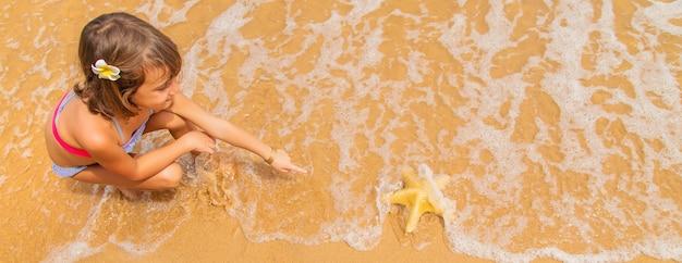 Un niño con una estrella de mar en sus manos en la playa.