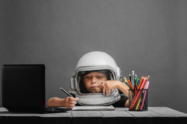 El niño estudia a distancia en la escuela, con un casco de astronauta. de vuelta a la escuela