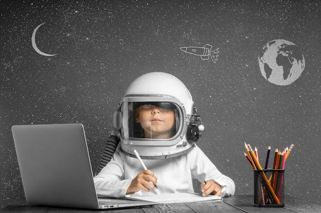 El niño estudia a distancia en la escuela, usando un casco de astronauta. de vuelta a la escuela