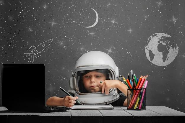 El niño estudia a distancia en la escuela, usando un casco de astronauta.