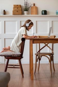 Niño estudiando en casa full shot