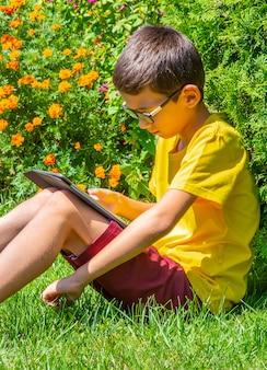 Niño estudiando en un parque leyendo información sobre una mesa