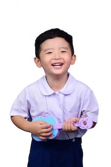 Niño estudiante asiático en uniforme escolar tocando el trazado de recorte de guitarra de juguete