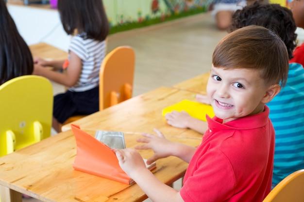 Niño de etnia caucásica del muchacho que sonríe en sala de clase con los amigos en la escuela de jardín de la infancia.