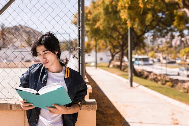 Niño étnico leyendo el libro con cuidado