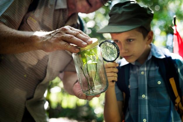 Niño examinando una planta con una lupa