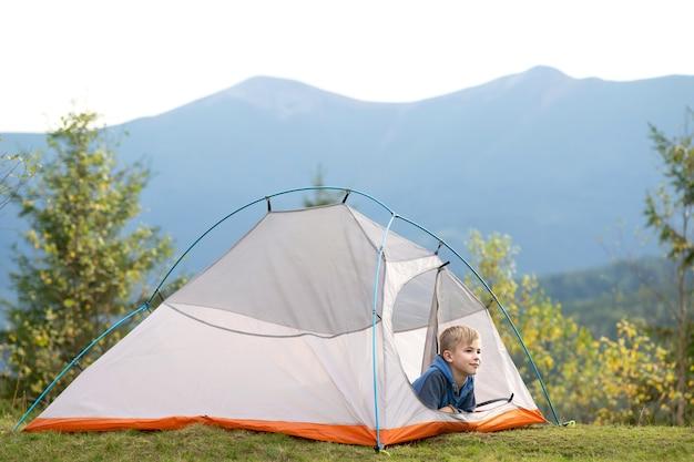 Niño excursionista sentado dentro de una carpa en el camping de montaña disfrutando de la vista de la naturaleza