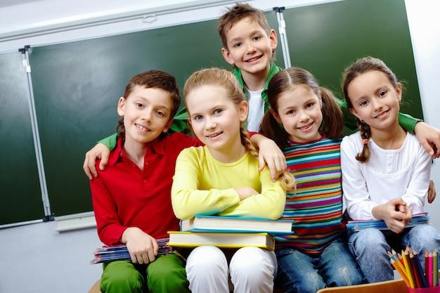 Niño feliz abrazando a sus compañeros de clase