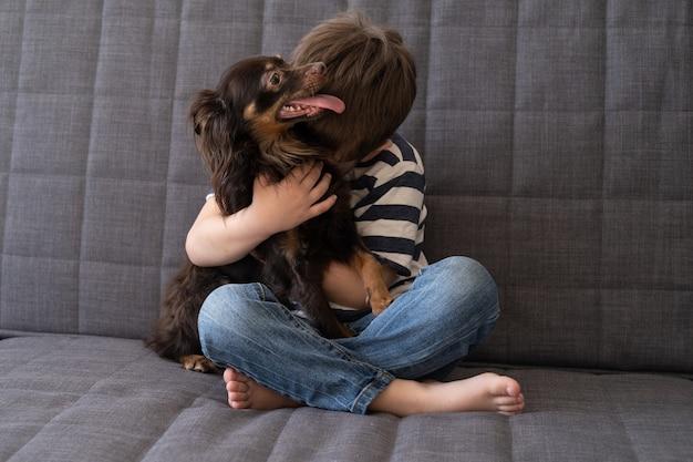 Niño feliz abrazo abrazo divertido terrier de juguete ruso marrón. concepto de cuidado de mascotas.