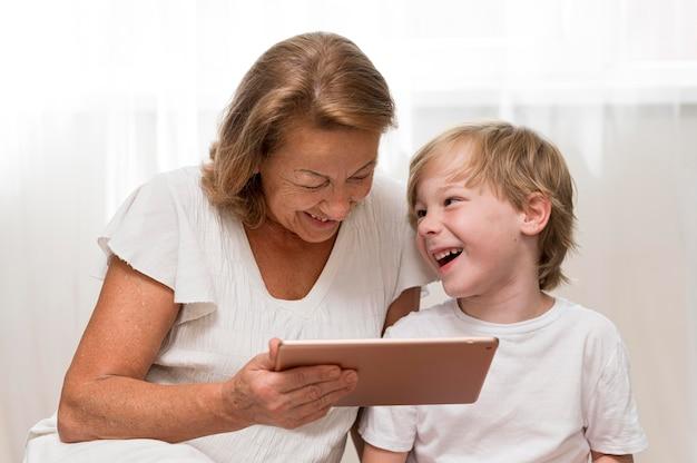 Niño feliz y abuela con tableta