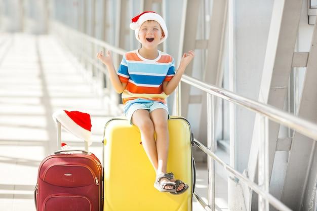Niño feliz en el aeropuerto en gorro de navidad