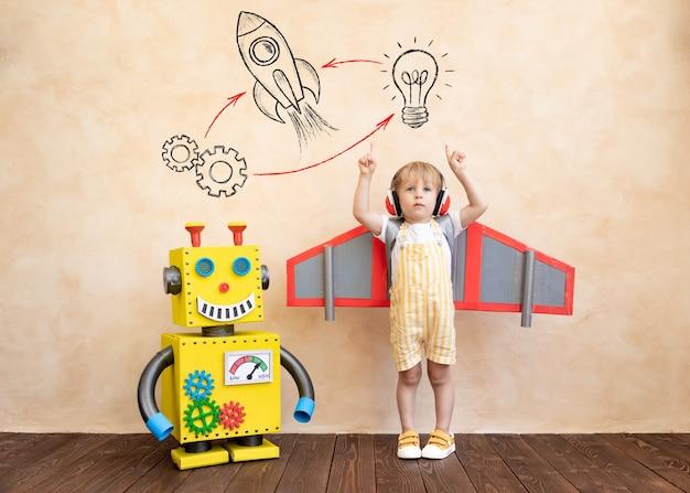 Niño feliz con alas de cartón con robot hecho a mano de juguete.