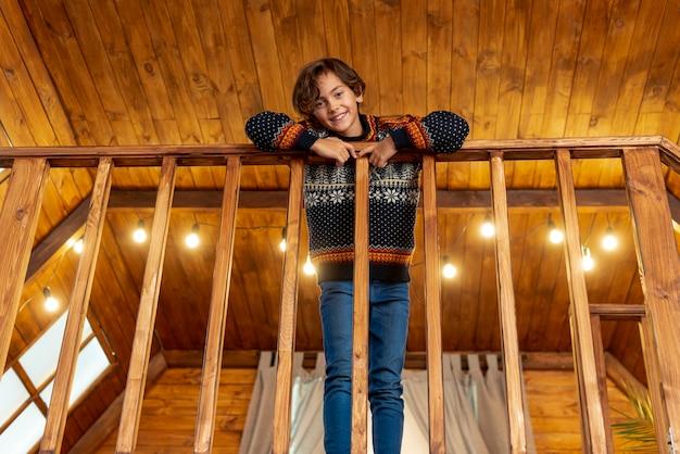 Niño feliz de ángulo bajo posando cerca de la balaustrada