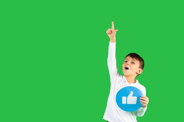 Niño feliz apunta hacia arriba con el dedo índice sosteniendo un cartel similar