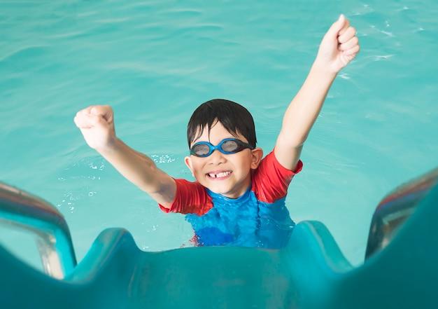 Niño feliz asiático que juega el resbalador en piscina
