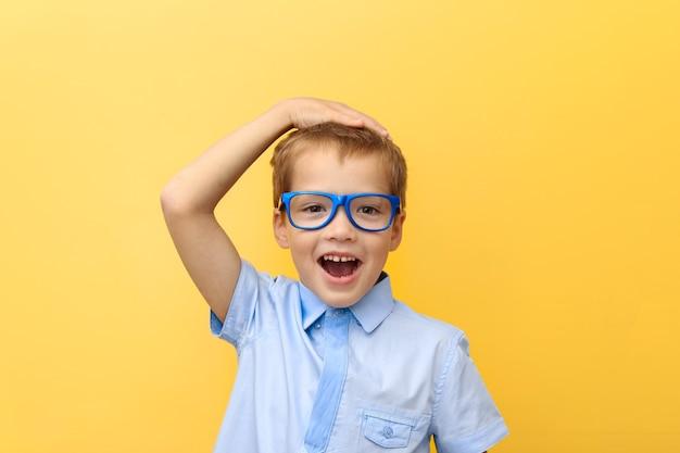 Un niño feliz y asustado con una camisa y gafas se agarró la cabeza contra una pared amarilla