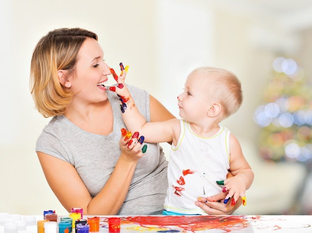 Niño feliz se basa en el rostro de su madre en casa.