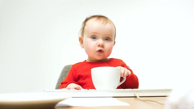 Niño feliz bebé niña niño pequeño sentado con el teclado de la computadora aislado en un blanco