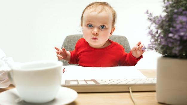 Niño feliz bebé niña niño pequeño sentado con el teclado de la computadora aislado sobre un fondo blanco.