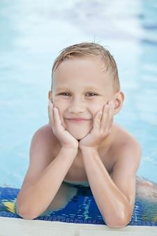 Niño feliz con cabello rubio sonriendo sentado en la piscina