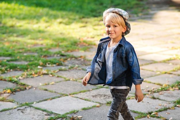 Niño feliz caminando en el parque. niño con estilo posando al aire libre. niño lindo en traje de verano. niño con sombrero y ropa de moda. niño divirtiéndose afuera en el parque.