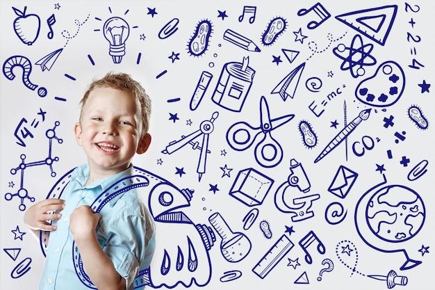 Niño feliz con una camisa ligera va a la escuela por primera vez.