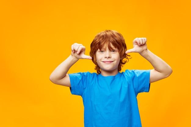 Niño feliz con una camiseta azul muestra su pulgar y sonríe