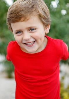 Niño feliz con camiseta roja en el jardín