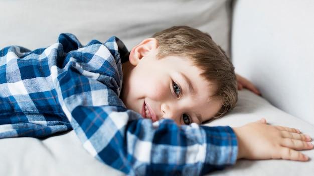 Niño feliz en casa tendido en el sofá