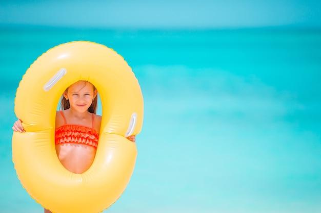 Niño feliz con círculo de goma inflable divirtiéndose en la playa