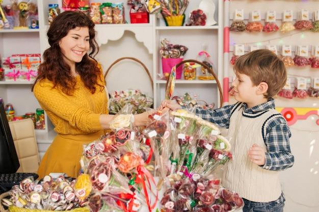 Niño feliz comprando dulces en la tienda