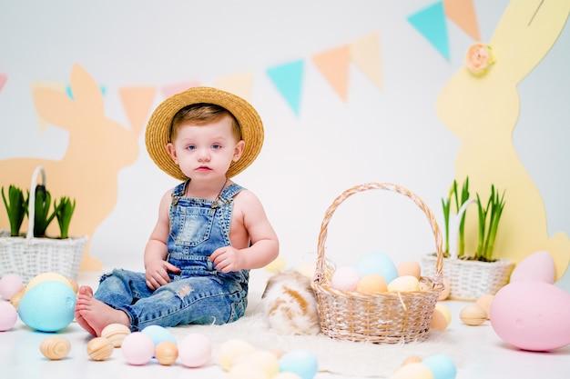 Niño feliz con conejito esponjoso cerca de huevos de pascua pintados