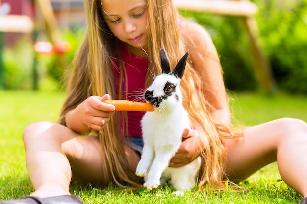 Niño feliz con conejito mascota en casa en el jardín