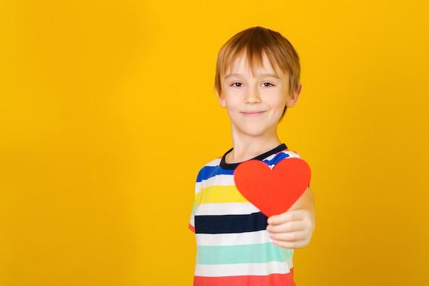 Niño feliz con corazón rojo sobre amarillo