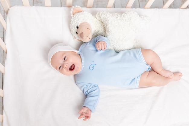 Niño feliz en la cuna con el juguete del oso de peluche, los niños y el concepto de nacimiento