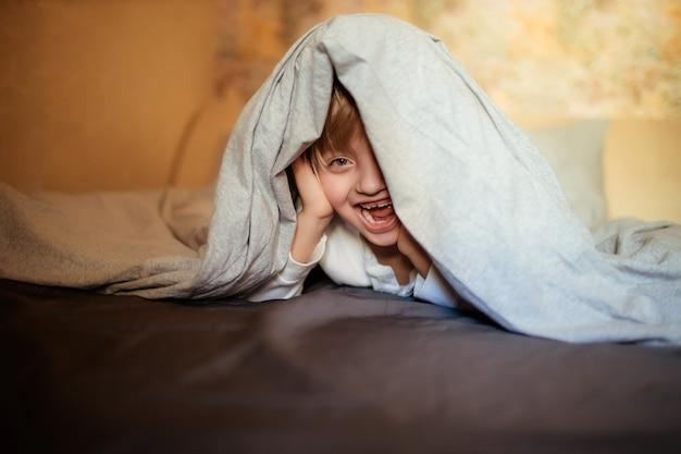 Niño feliz debajo de la manta en la cama